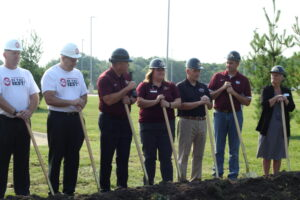 Leaders in hardhats with shovels