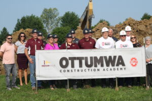 Group gathered behind Construction sign.